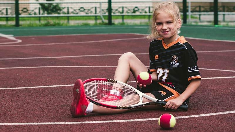 Girl with beginner tennis balls
