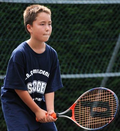 Young boy playing tennis.